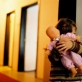 A young girl hides behind her doll at an orphanage in Tuzla for abandoned children. Kate Holt.