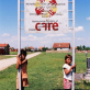 Children stand by the sign for the Village of Dobraje, where Care completed a drinking water project. Kate Holt.