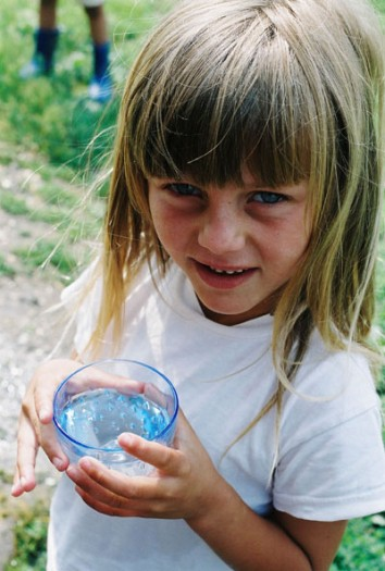 A young girl drinks water in the village of Dobraje, Kosova. Kate Holt.