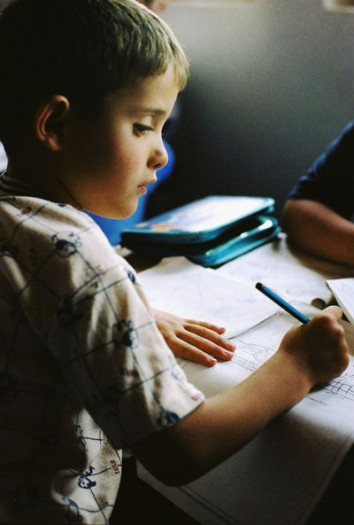 A young boy draws a picture in a playgroup organized by the women's organization in Maxjunaj. Kate Holt.