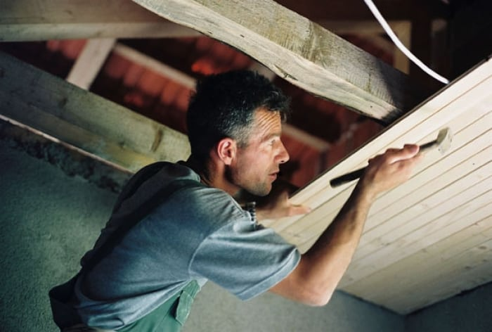 A worker fixes in a roof in a reconstruction project funded by Care. Kate Holt.