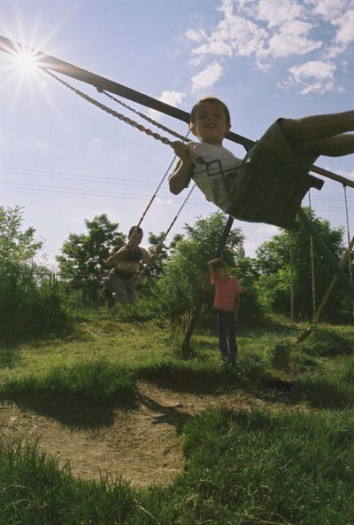 Children play on swings in a village where Care supports local education projects near Zhiti, Kosova. Kate Holt.