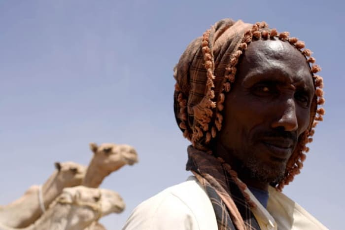 A pastoralist at a borehole run by Care. His camels, in the background, are all that remains of his herds. Kate Holt.