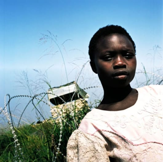 A young girl stands in front of a UN watch tower, situated 6 meters from her family's tent. Kate Holt.