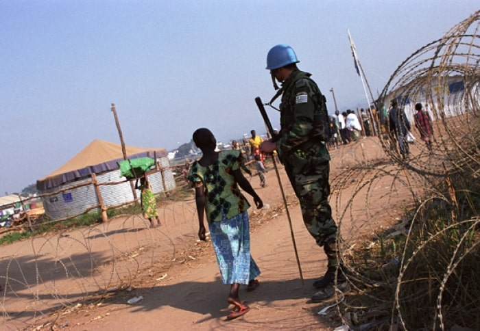 A girl walks passed a Uruguayan soldier at the entrance of the IDP camp in Bunia. Kate Holt.