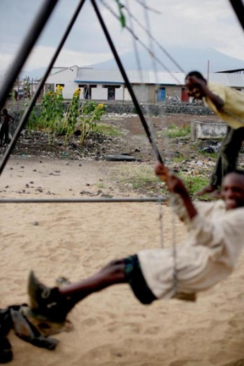 Children from the street children project in their playground with Goma's volcano in the distance. Kate Holt.