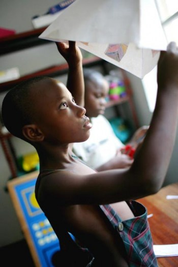 A young girl from the Inuka Housing project prepares her entry of a paper lantern.