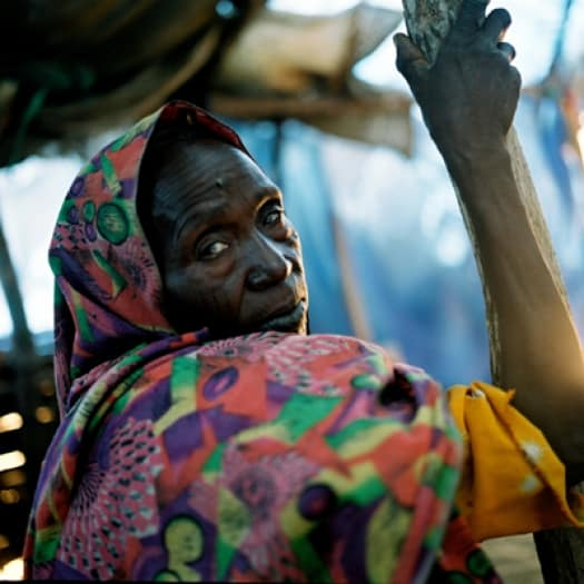 Halima lives with her only remaining grandson, Ismail (not seen), in Krindigg camp, Darfur. Kate Holt.