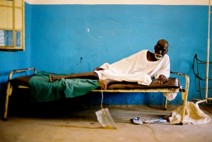 Many elderly people, like this man who lies ill in Nyala Hospital, have been abandoned in hospital. Kate Holt.