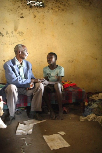 John Riukaamya sits with one of his orphaned grandchildren who is HIV positive. Kate Hole.