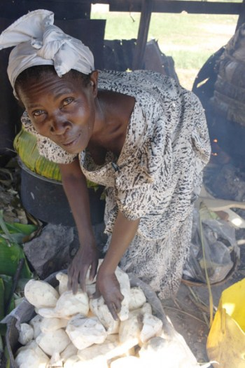 A woman cooks manioc to sell by the roadside in an income generation project for elderly women. Kate Holt.