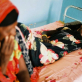 A woman watches over a female relative who is suffering from acute dehydration. Kate Holt.