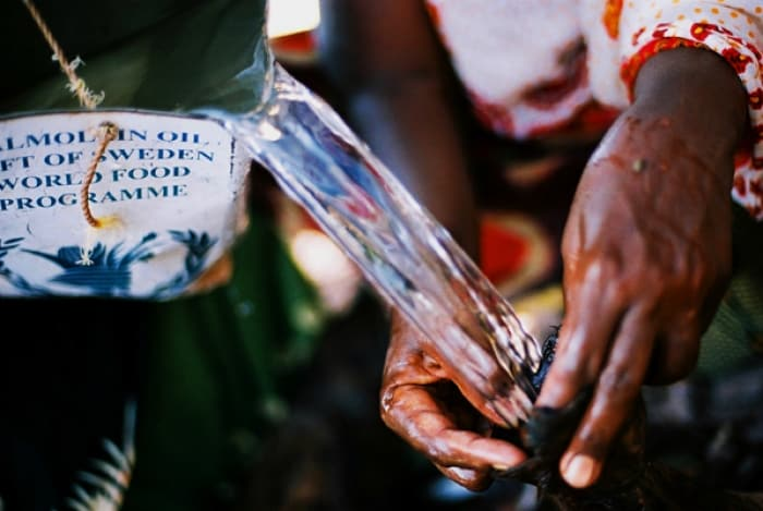 Water is collected in a goat skin bag at a collection point near Tadjoura. Kate Holt.