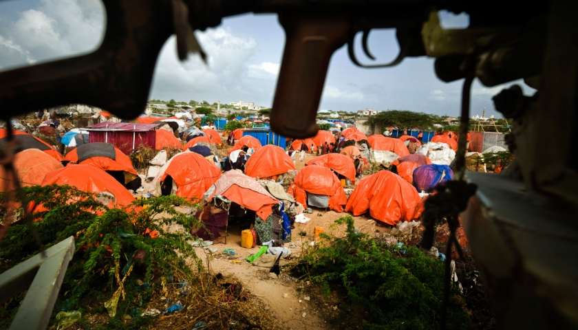 Orange plastic shelters, used as temporary accommodation by displaced people, sprawl into the distance beneath the protecting body of an AMISOM machine-gun in the Badbado Camp in Mogadishu. Kate Holt.