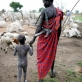 A Mundari Cattle herder with his young son in a cattle camp in South Sudan. Kate Holt.