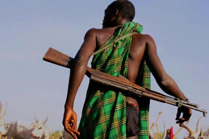 A Mundari Cattle herder watches over his cows in a cattle camp with a rifle strapped to his back. Kate Holt.
