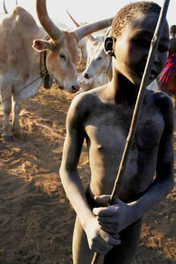 A young Mundari boy leans on his spear in a cattle camp outside of Juba. Kate Holt.