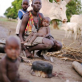 A woman sits with her young family in a cattle camp, South Sudan. Kate Holt.