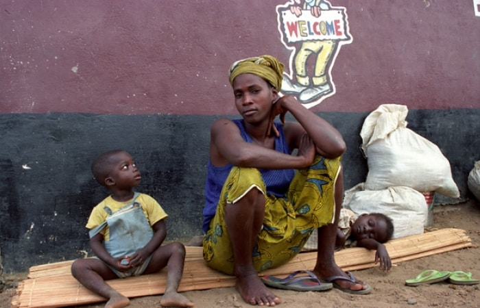 A woman and her family wait for help at a Transit Centre near Monrovia. Kate Holt.