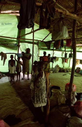 A family sit in their tent in a transit centres for IDP's in Ganta. Kate Holt.