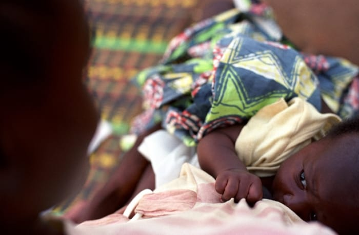 A woman feeds her baby in Sanniquellie Hopsital, Nimba County. Kate Holt.