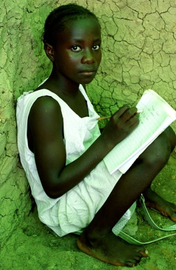 A young girl sits on the floor in her classroom, because there are no desks or chairs. Kate Holt.