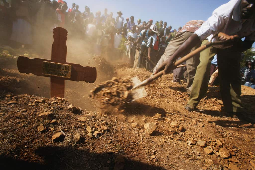 A grave digger shovels earth over the  coffin of formerMP David Kimutai Too, at his families home in Ainamoi, Western Kenya on 9 February. Kate Holt.