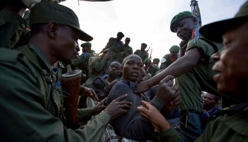 A bleeding Congolese man cuffed by Congolese government troops (FARDC) is taken away with 25 others by FARDC soldiers at the Kibati checkpoint north of Goma, eastern Congo. Kate Holt.