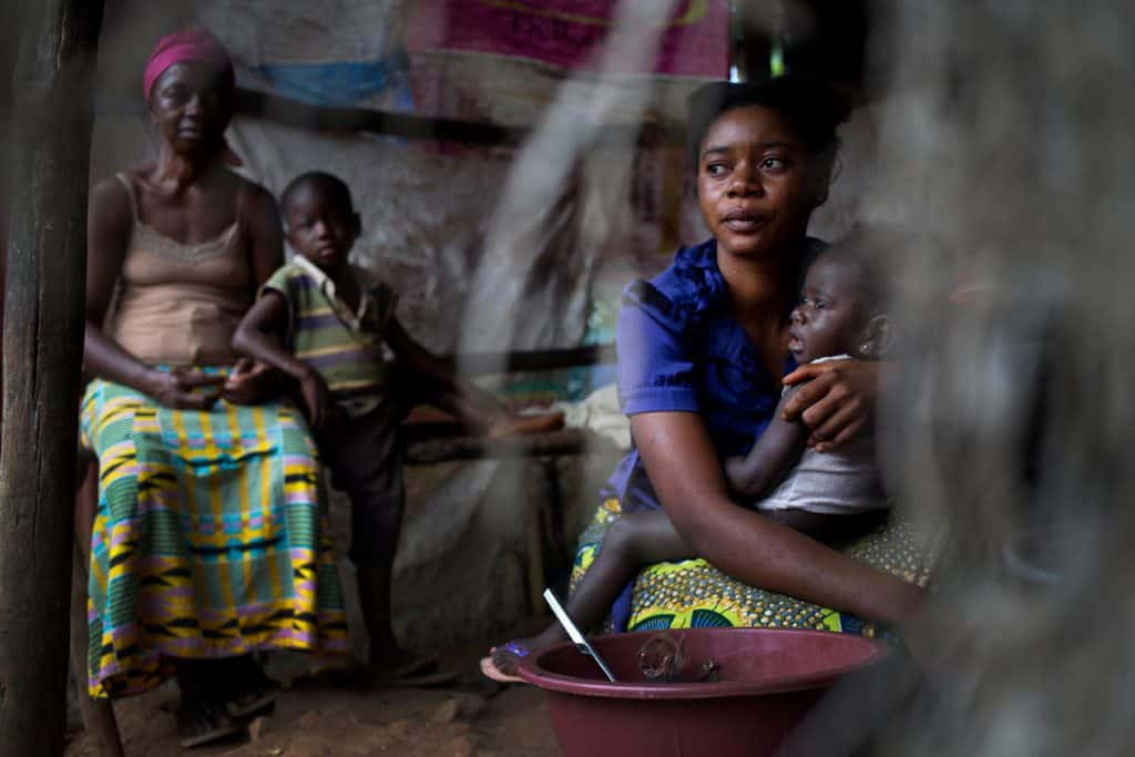 Kadiatu Bangora, who is 22 years old, poses for a photograph with her baby at the road side food stall. Kate Holt.