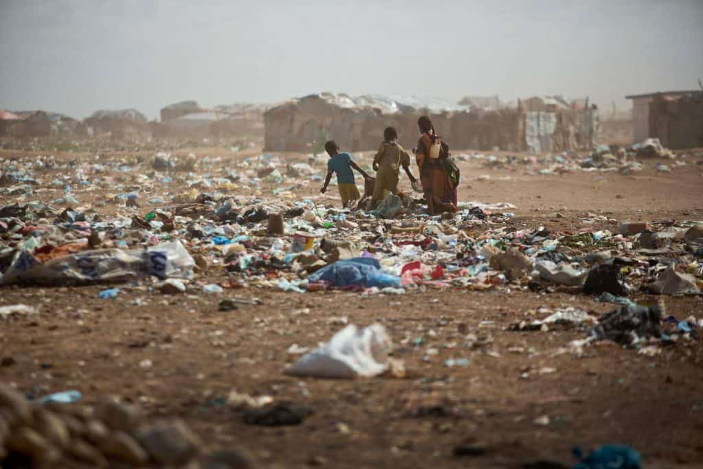 Children collect rubbish in a dust storm in the Shabelle IDP settlement in  Garowe, Somalia Tuesday, July 1, 2014. Kate Holt.
