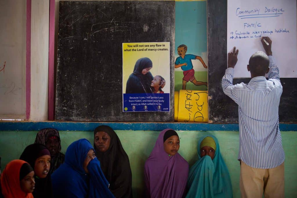 Women sit in a community meeting, organised by UNICEF,  to raise awareness about the dangers of FGM while a community mobiliser. Kate Holt.