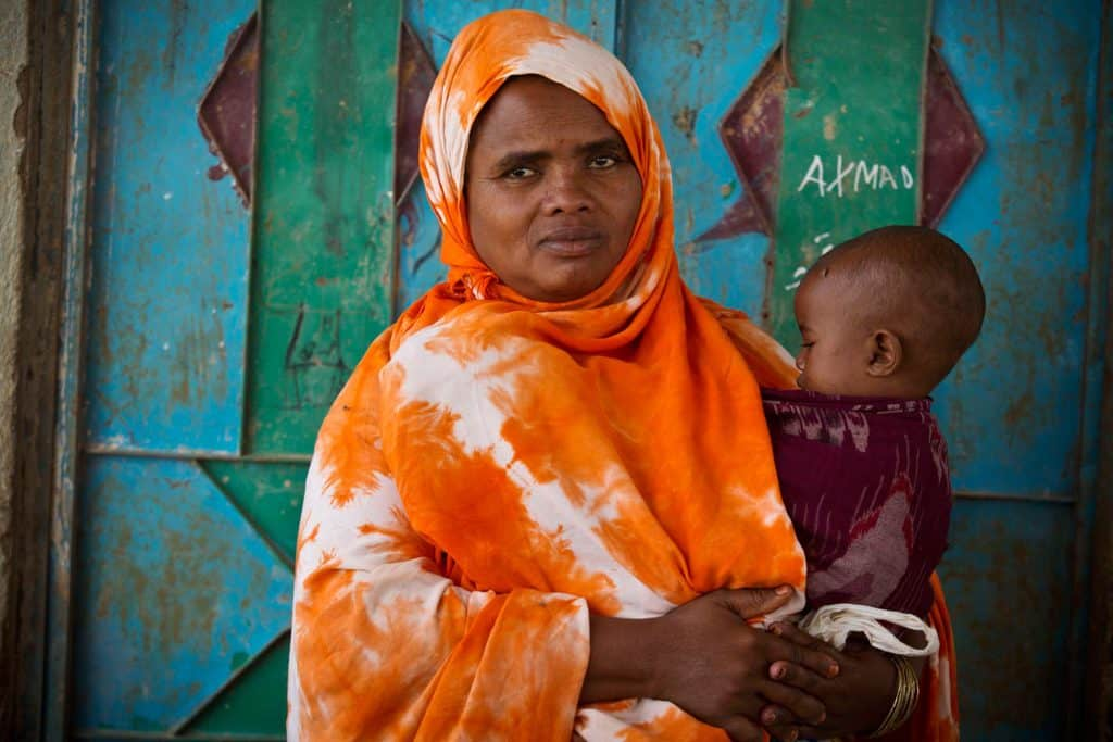 Rahmo Hassan Aden, who has lost three chidren during child birth because of FGM, poses for a photograph with her baby. Kate Holt.