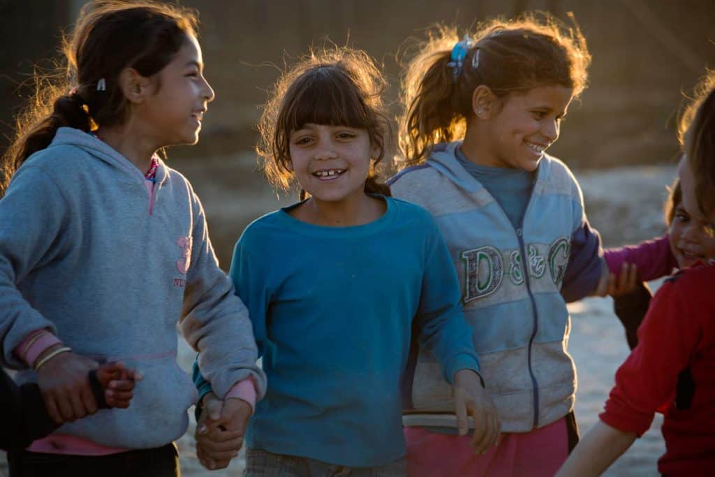 Young girls play a game in the evening light in a settlement for refugees from Syria in the town of  in  Zahle, Lebanon. Kate Holt.