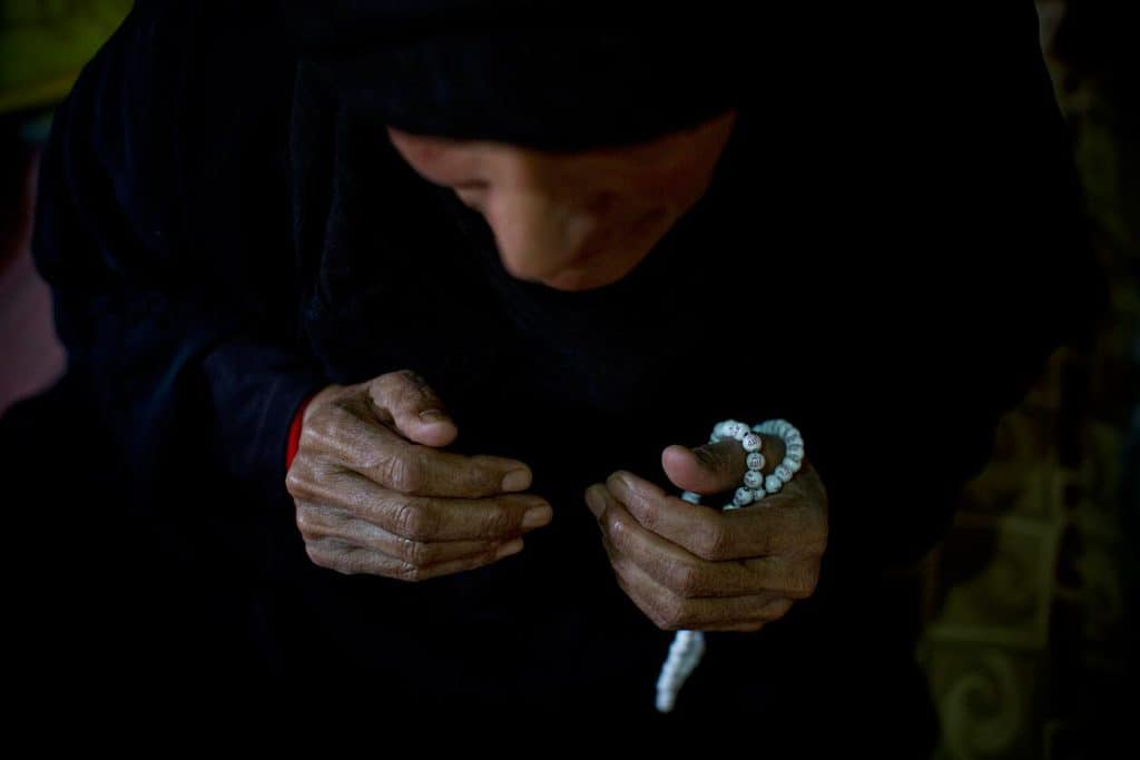 Fatima, who is 80, fingers her prayer beads while she prays in shelter she is living in in a settlement for Syrian refugees. Kate Holt.