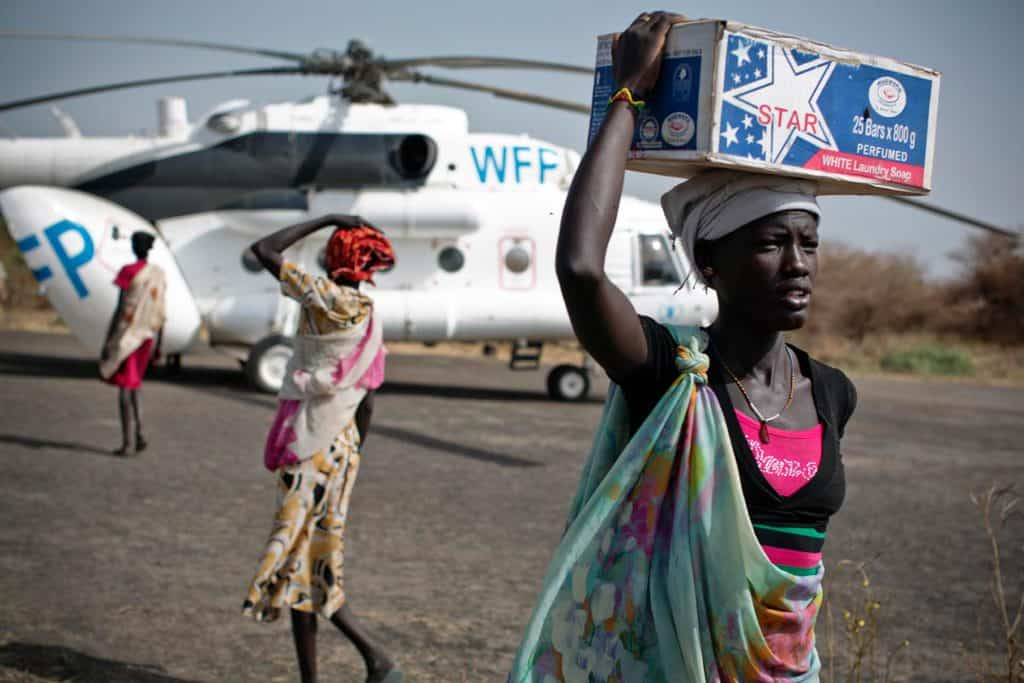 Women carry emergency food supplies on their head from a World Food programme helicopter that has just landed in Thanyang. Kate Holt.