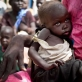 A woman holds her severely malnourished child while they wait to be registered to receive food aid. Kate Holt.