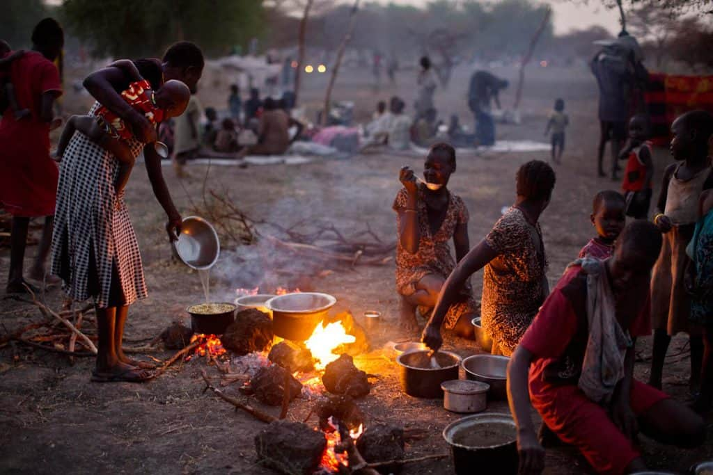 Women and their children, who have been displaced by ongoing fighting, camp outside in the open air. Kate Holt.