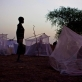 A young boy stands by his mosquito net that is his families only shelter at night, in Thanyang. Kate Holt.