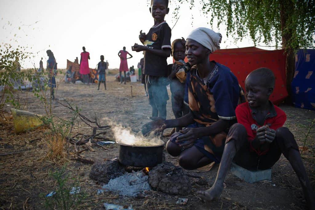 Nyaki Masha a mother of six, who has had two children who have died from hunger and one who was killed in the war, cooks. Kate Holt.
