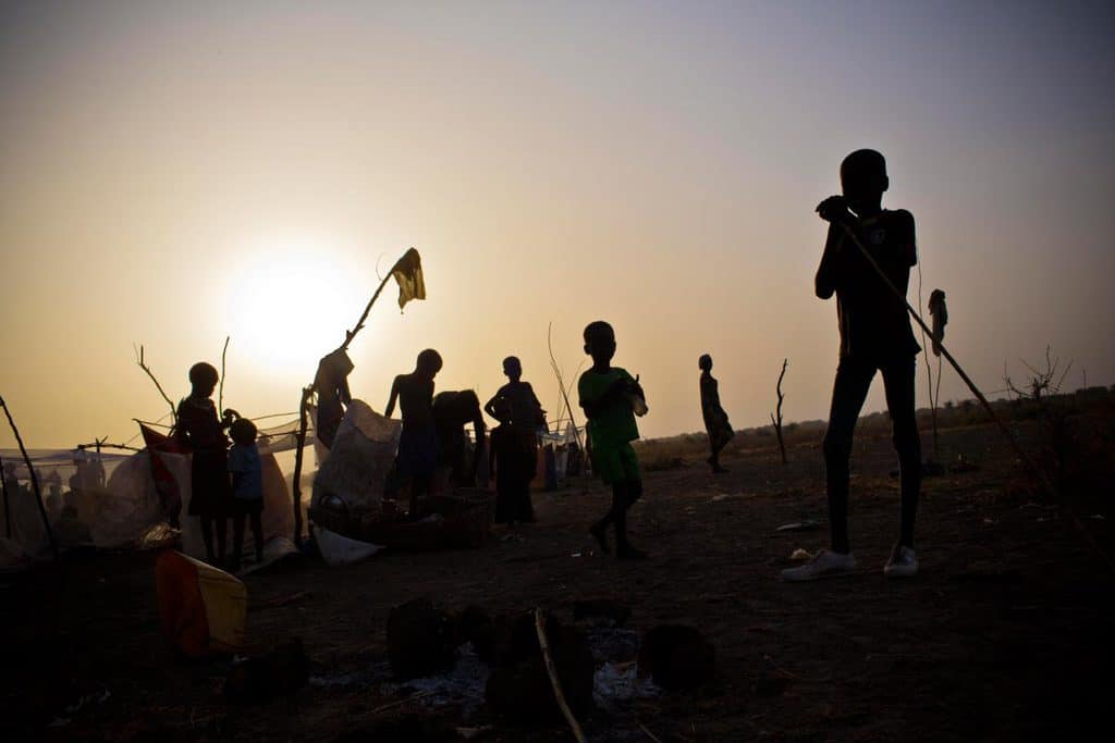 Women and their children, who have been displaced by ongoing fighting, camp outside in the early morning. Kate Holt.