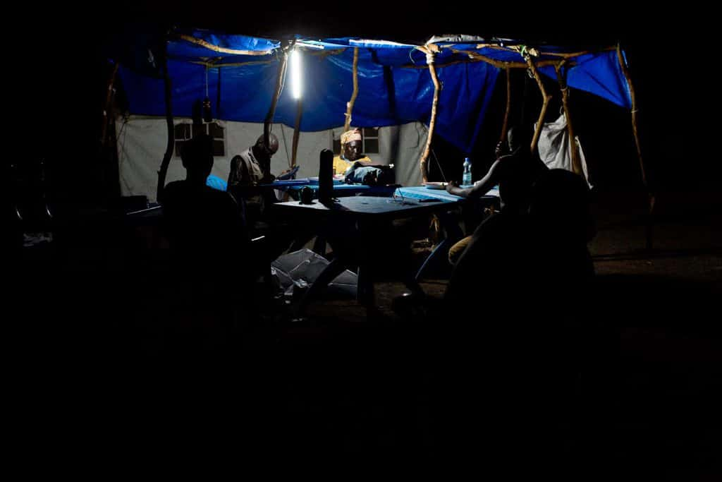 Staff members from UNICEF and the World Food Programme work late into the night using a solar power lamp. Kate Holt.