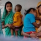Women poses for photographs with their baby at a community centre, while waiting for their babies to be weighed. Kate Holt.