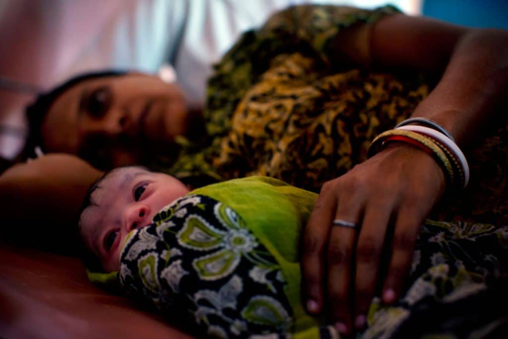 A mother holds her newborn baby in Kolibera health centre near to Ranchi, India Friday, May 30, 2014. Kate Holt.