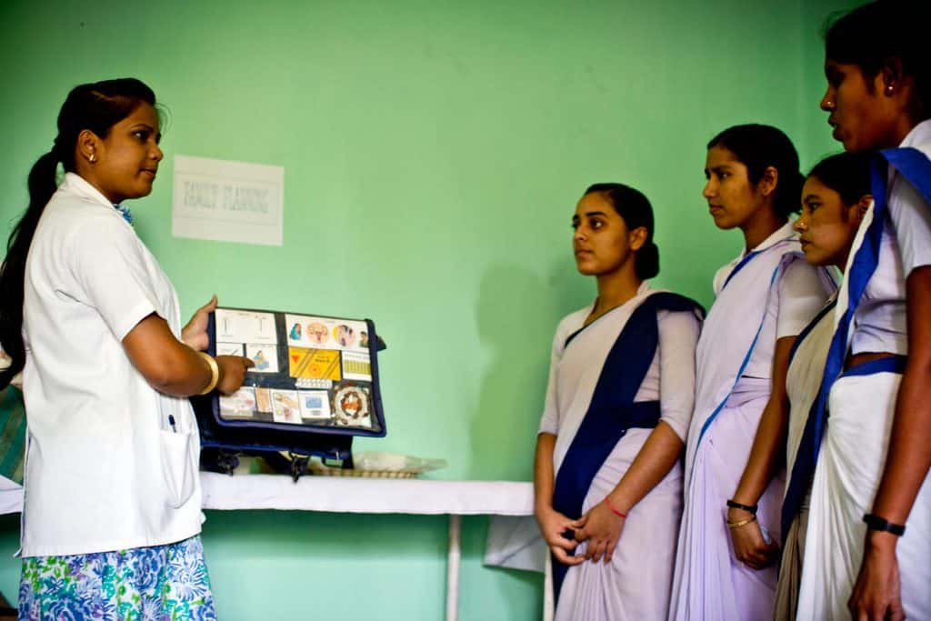 Girls who are attending the midwifery trainee college that has been rehabilitated with the help of MCHIP listen to a talk. Kate Holt.