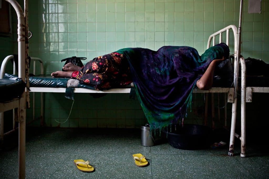 A woman sleeps in a female ward in Benadir Hospital. Many women undergo severe problems in child birth. Kate Holt.