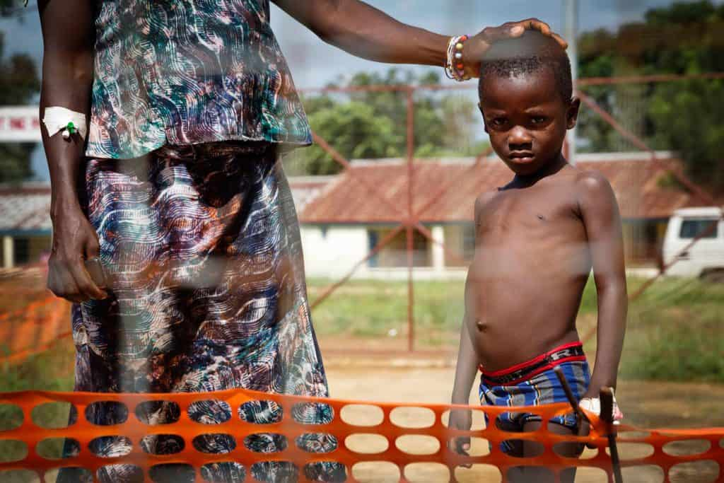 A young boy poses for a photograph with his mother in the quarantine area at the PTS 1 Ebola Treatment Centre. Kate Holt.