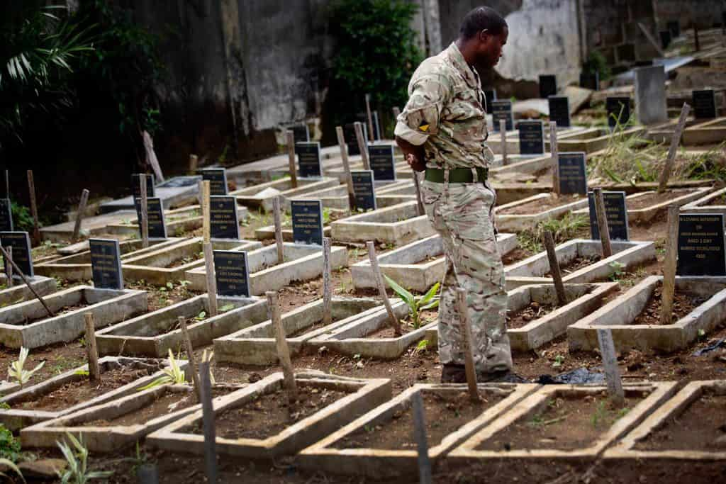 Sergent Solomon Kamara, who is part of the  Joint Inter Agency Task Force ( JIATF) walks down a line of children's graves. Kate Holt.