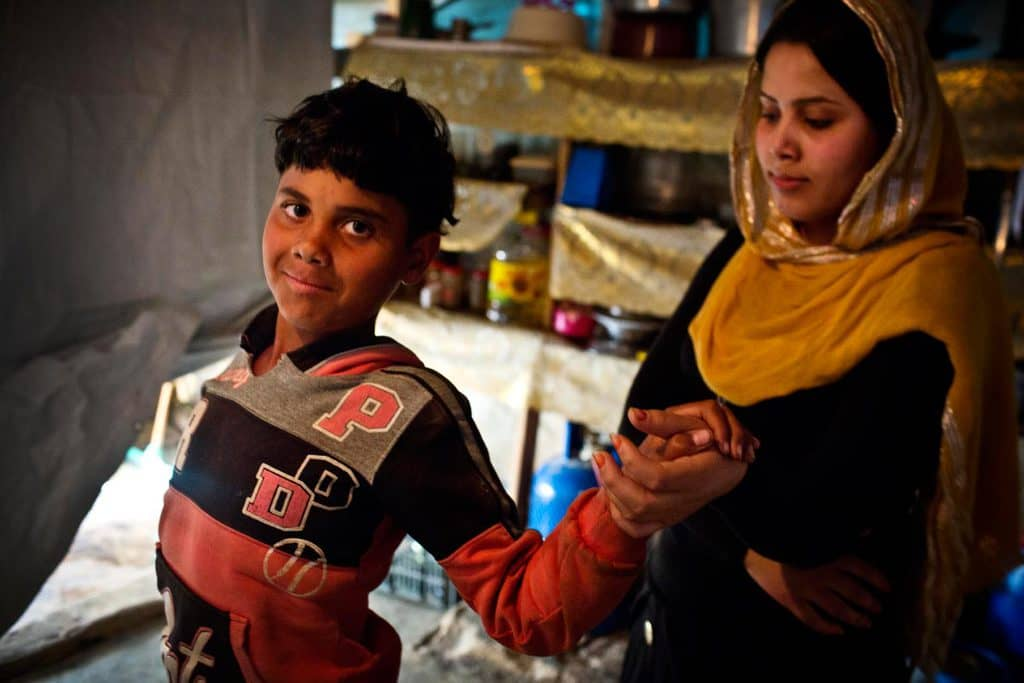 Ali, who is 9 years old, and disabled, is helped to walk by his sister Fatima, who is 18. Kate Holt.