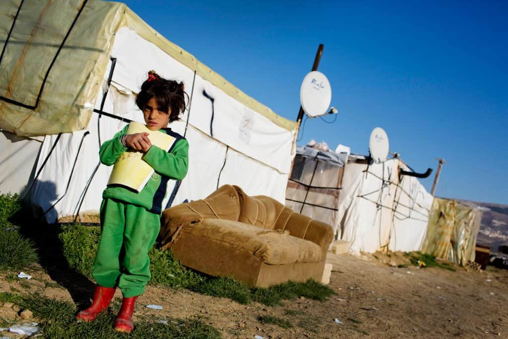 A young girl holds a school book outside the shelter that she lives in with her family in a settlement for refugees. Kate Holt.