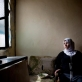 Fatime Sowan, 33 years old, and a refugee from Syria, poses for a photograph in the house that she and her family are renting. Kate Holt.